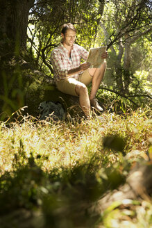 Hiker sitting on tree trunk reading map - TOYF000403
