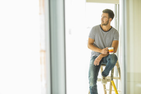Young man having a coffee break from renovating - UUF004164