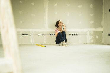 Young woman renovating sitting at blank wall - UUF004171