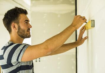 Young man renovating drawing marking at wall - UUF004180