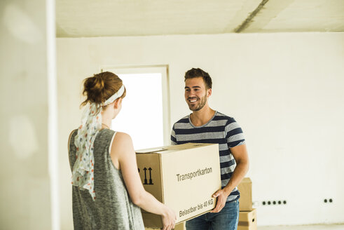 Young couple carrying cardboard box together - UUF004187