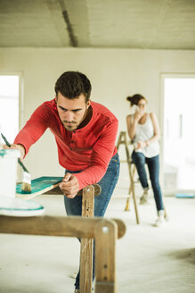 Young man painting wooden board with woman in background on the phone - UUF004210