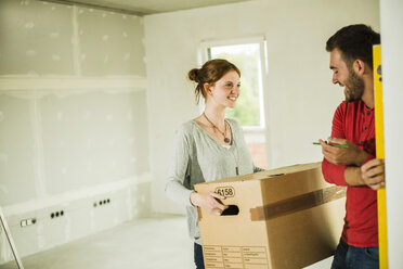 Smiling young couple moving house - UUF004215