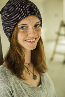 Portrait of smiling young woman wearing a cap - UUF004227
