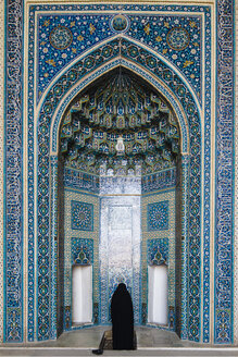 Iran, Yazd, woman wearing a chador praying at the Mihrab of Jameh Mosque - FL000978