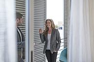 Businesswoman smoking in a hotel room - ZEF004913