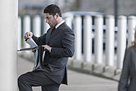 Businessman taking papers out of briefcase - ZEF005871