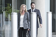 Businessman and businesswoman walking outside of hotel - ZEF005872