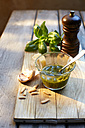 Glass of homemade basil pesto, ingredients and a pepper grinder - KSWF001481