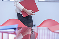 Woman with folders in an office - ZEF005068