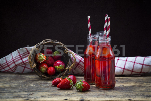 Three glass bottles of homemade strawberry lemonade and wickerbasket of strawberries - LVF003361