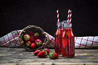 Three glass bottles of homemade strawberry lemonade and wickerbasket of strawberries - LVF003361