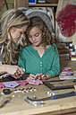 Mother and daughter doing crafts in home garage - ZEF004860