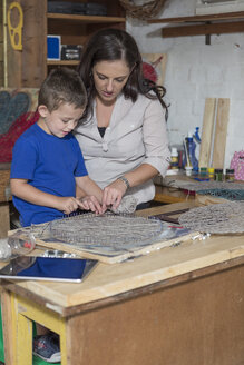 Mother and son doing crafts in home garage - ZEF004863