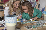 Mother and daughter doing crafts in home garage - ZEF004866