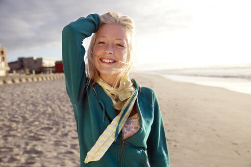 Portrait of smiling young woman on beach at sunrise - TOYF000431