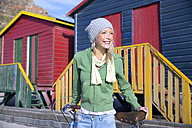 Smiling young woman with bicycle in front of colorful beach huts - TOYF000458