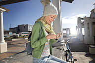 Young woman sitting outdoors looking on cell phone - TOYF000468
