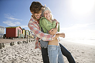 Playful young couple on beach - TOYF000473