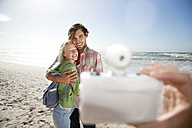 Happy young couple on beach being photographed - TOYF000615