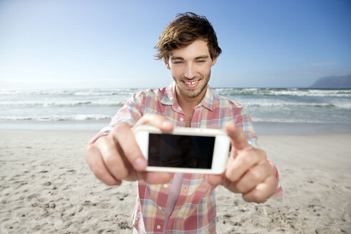 Young man taking selfie on the beach - TOYF000482