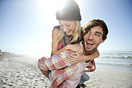 Young man carrying girlfriend piggyback on beach - TOYF000485