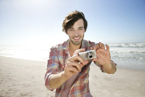 Young man taking picture on the beach - TOYF000493
