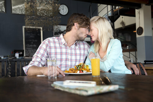 Young couple in a restaurant having lunch - TOYF000513
