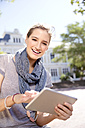 Portrait of smiling young woman using digital tablet outdoors - TOYF000528