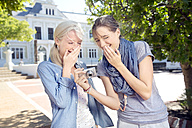 Two laughing young women outdoors looking at camera - TOYF000534