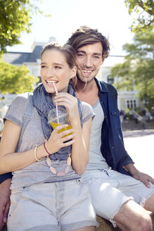 Smiling young couple outdoors with soft drink - TOYF000539
