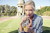 Young woman in park with soft drink - TOYF000551