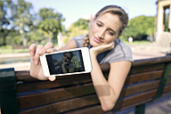 Young woman on park bench taking a selfie - TOYF000560