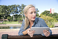 Young woman using digital tablet on park bench - TOYF000563