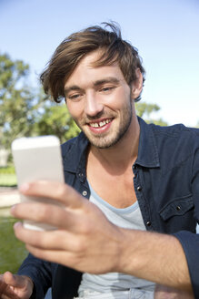 Smiling young man in park taking a selfie - TOYF000566