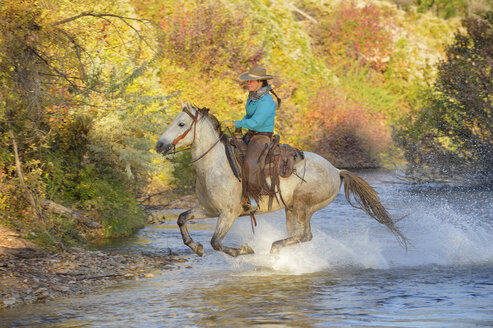 USA, Wyoming, cowgirl riding his horse across river - RUEF001590