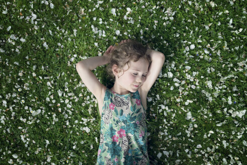 Little girl lying on meadow with scattered apple blossoms - OPF000057