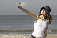 Netherlands, Scheveningen, young woman taking a selfie on the beach - GDF000726
