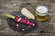 Sliced red radish and bread on metal tray and glass of beer - SARF001785