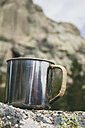 Abandoned metal cup on a rock - ABZF000044