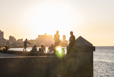 Cuba, Havana, Malecon, young people at sunset - FB000386