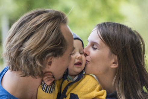 Father and mother kissing their little son - FBF000407