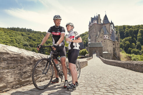 Germany, Rhineland-Palatinate, US American couple standing in front of Eltz Castle with their tandem - MF002071