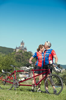Germany,  Rhineland-Palatinate, US American couple kissing in nature in front of Eltz Castle with their tandem - MF002078