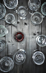 Glass of red wine and empty wine glasses on wood - KSWF001528