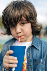 Boy drinking with straw from disposable cup - MGOF000227