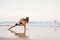 Sri Lanka, Kabalana, young woman practicing yoga on the beach - WV000746