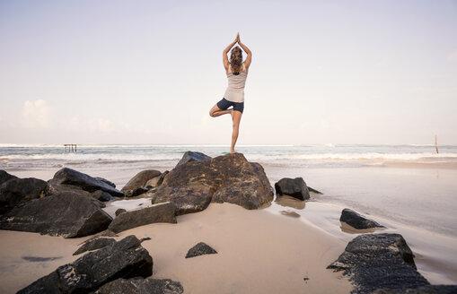 Sri Lanka, Kabalana, young woman practicing yoga on the beach - WV000750