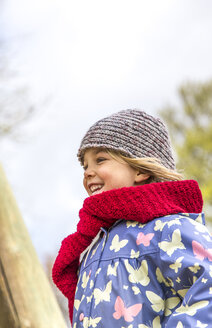 Happy little girl wearing red scarf and wool cap - JFEF000655