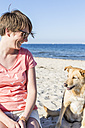 Germany, Kiel, smiling woman sitting with her dog on sandy beach - JFEF000671
